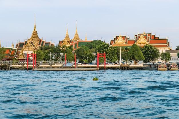 Opinião da paisagem do rio de chao phraya com wat phra kaew e do palácio grande no fundo.
