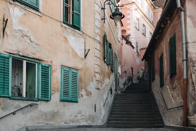 Opinião da rua da escada de sibiu entre casas históricas velhas.