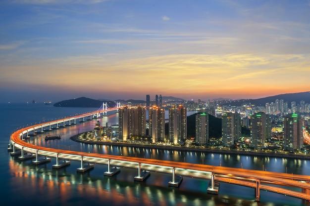 Opinião da skyline da cidade de busan no distrito de haeundae, praia de gwangalli com o cais do iate em busan, coreia do sul.