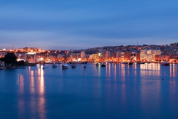 Opinião da skyline da frente marítima de valletta como visto de sliema, malta. construções históricas iluminadas após o por do sol.