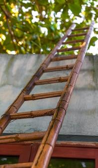 Opinião de baixo ângulo da escada de bambu, maneira ao céu.