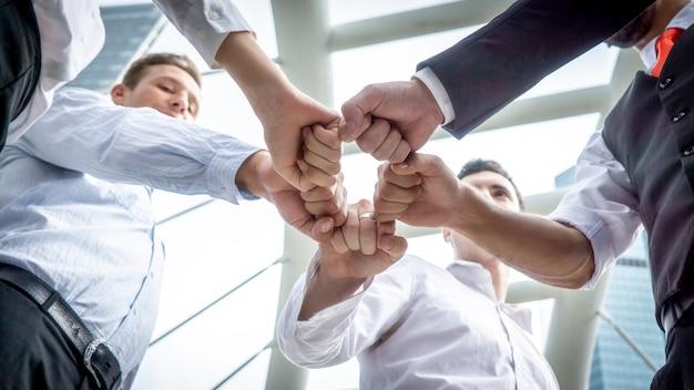 Opinião de baixo ângulo dos amigos que empilham as mãos contra