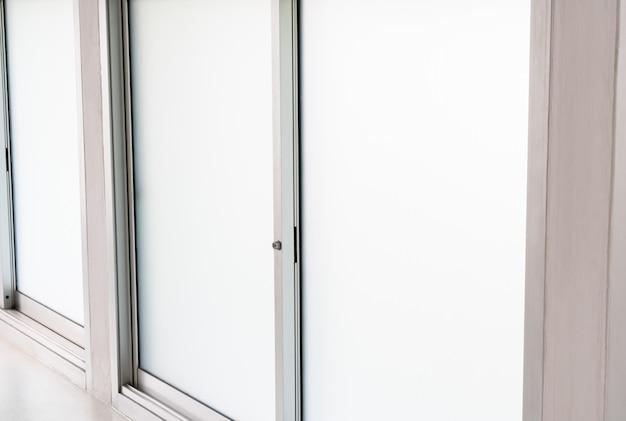 Opinião de janela de vidro desobstruída de aço inoxidável dentro da casa, frame de painéis dobro branco fechado interior