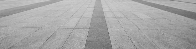 Opinião de perspectiva da pedra cinzenta monótono do tijolo na terra para a estrada da rua.