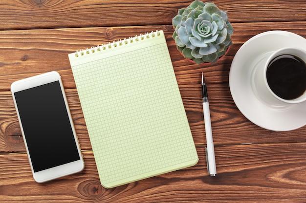 Opinião de tampo da mesa de mesa de escritório. bloco de notas com páginas em branco na mesa de madeira
