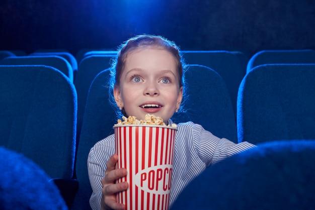 Opinião dianteira a menina entusiasmado que come a pipoca do queijo e que olha filme surpreendente no cinema.