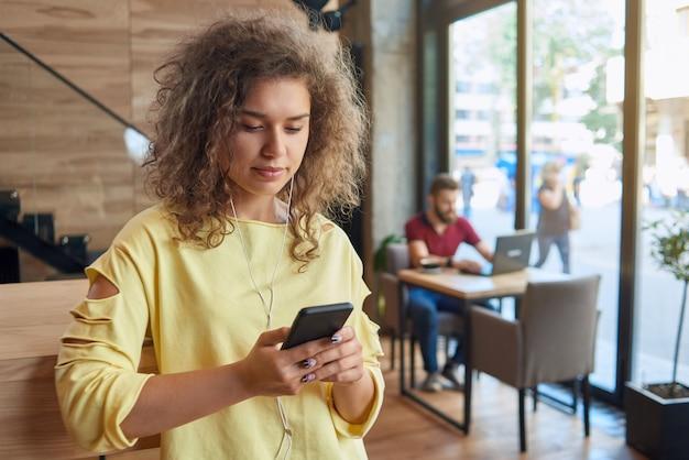 Opinião dianteira o estudante encaracolado que desgasta a blusa amarela que escuta a música.