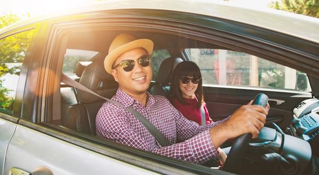 Opinião dianteira o homem asiático e a mulher dos pares engraçados do momento que sentam-se no carro. aproveitando o conceito de viagens.