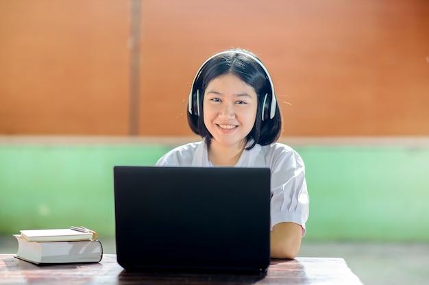 Opinião dianteira uma menina feliz do estudante que trabalha com um portátil na tabela em um parque da escola no verão.