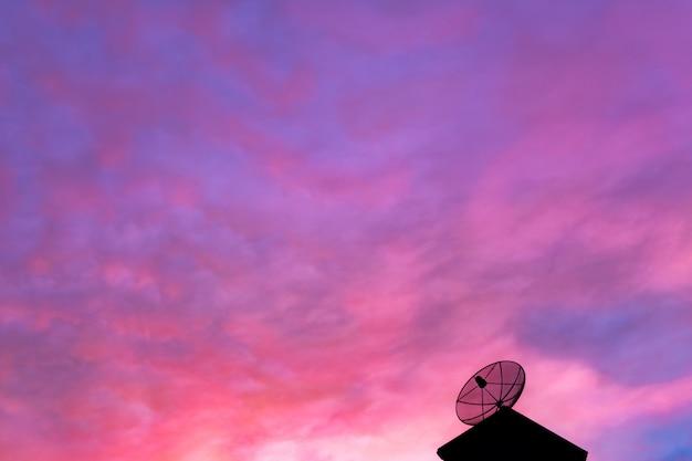 Opinião do céu da noite com as antenas no telhado da casa.