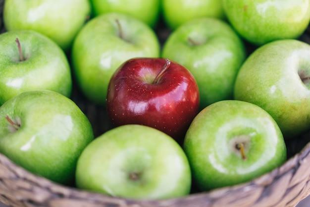 Opinião do close up do maçãs verdes coloridas saudáveis e uma maçã vermelha em uma cesta e os benefícios saborosos de cada um. ser diferente