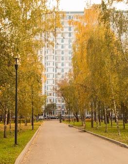 Opinião do outono de um edifício residencial de vários andares no final de um beco de asfalto, um parque na cidade com bétulas e lanternas, outono moscou.