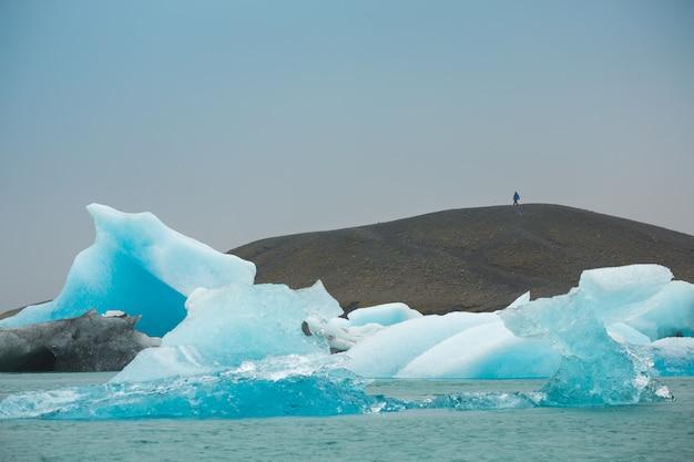 Opinião do panorama dos icebergs que flutuam na lagoa de jokulsarlon perto da costa do sul de islândia, conceito dos destinos de viagem