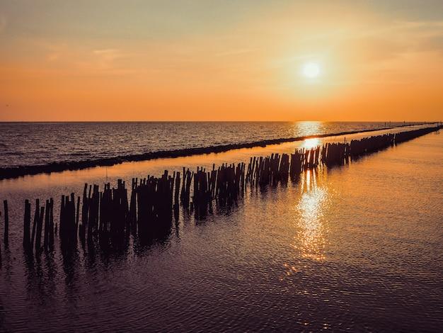 Opinião do por do sol do mar de pequeno de madeira no horizonte com silhueta dos povos e a paisagem alaranjada do céu.
