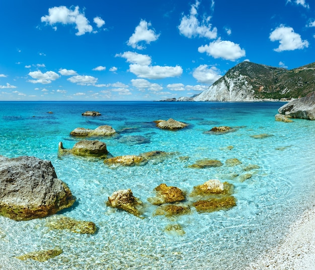 Opinião do verão da praia de petani com grandes pedras na água e o céu nublado de azul profundo kefalonia, grécia.