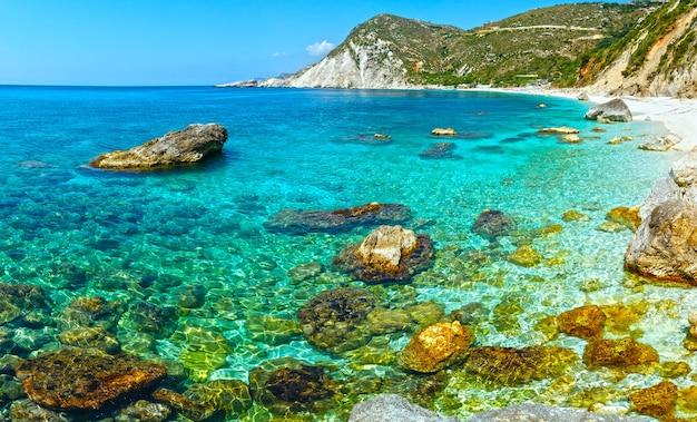 Opinião do verão da praia de petani com grandes pedras na água kefalonia, grécia. todas as pessoas não são reconhecidas.