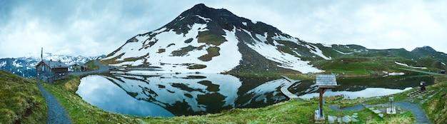 Opinião do verão tranquilo das montanhas dos alpes (reflexos no lago perto da estrada alpina de grossglockner). imagem composta de quatro fotos