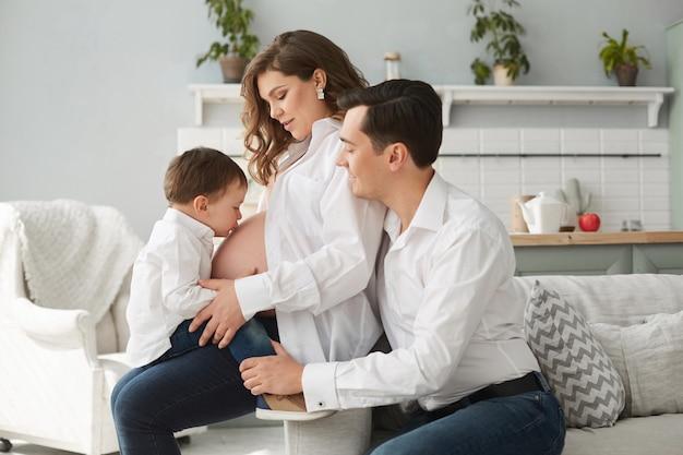 Opinião lateral a mulher gravida bonito que descansa com família em casa. menino beijando a barriga da mãe enquanto pai feliz sentado perto e abraçando a esposa. família alegre em camisas brancas. esperando bebê