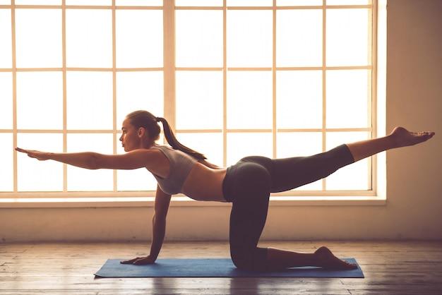 Opinião lateral a senhora nova bonita dos esportes que faz a ioga.