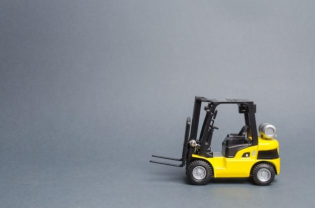 Opinião lateral amarela de caminhão de empilhadeira no fundo cinzento. armazém, equipamento, veículo