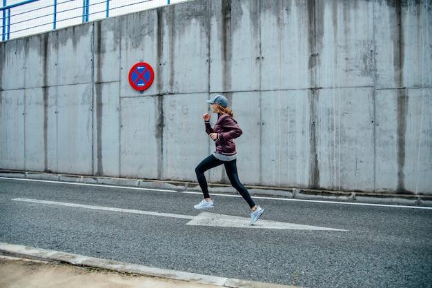 Opinião lateral uma jovem mulher de sorriso que corre na rua. vida urbana.