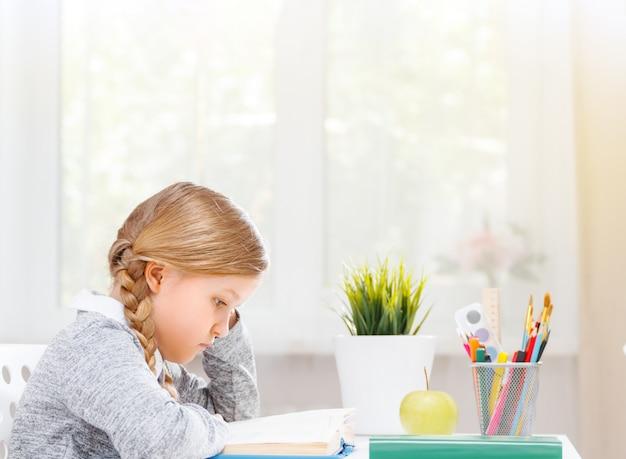 Opinião lateral uma menina pequena do estudante que senta-se em uma tabela que lê um livro.