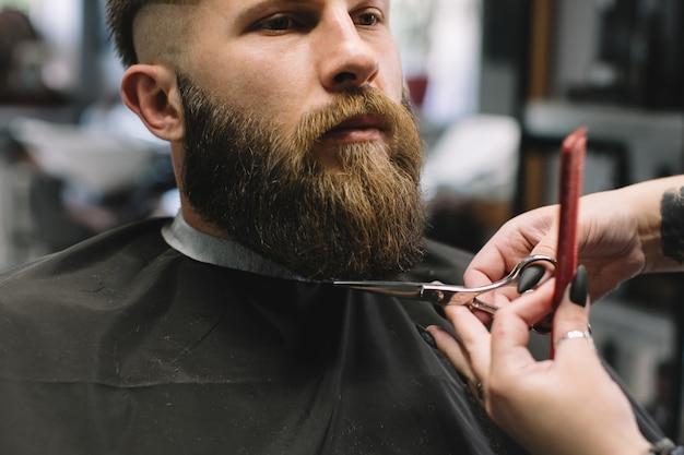 Opinião o homem farpado novo que obtém o corte de cabelo da barba pelo cabeleireiro no barbeiro.