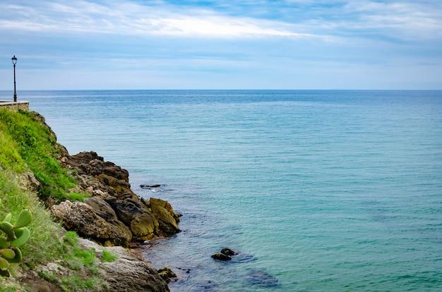 Opinião pitoresca do mar com as rochas da costa de sperlonga em itália.