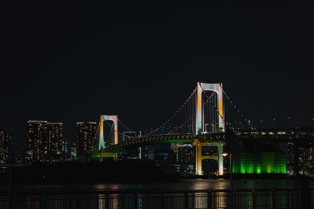 Opinião romântica da noite da cidade, ponte do arco-íris e marco da torre do tóquio, odaiba, japão.