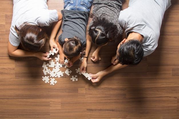 Opinião superior da família feliz que encontra-se no assoalho com resolver um enigma de serra de vaivém