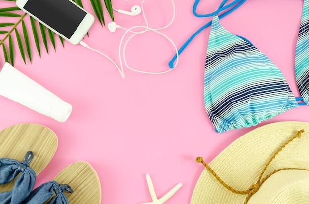 Opinião superior das coisas da praia da mulher. chapéu, biquíni, smartphone e chinelos