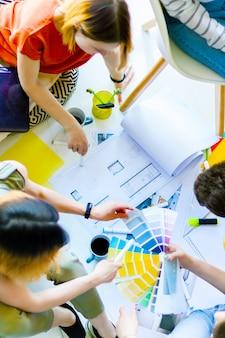 Opinião superior do close up os trabalhadores criativos que têm a reunião informal no espaço de escritórios claro. arquitetos e designers de interiores trabalhando no chão com amostras de cores, layouts de salas, suprimentos. conceito de trabalho em equipe.