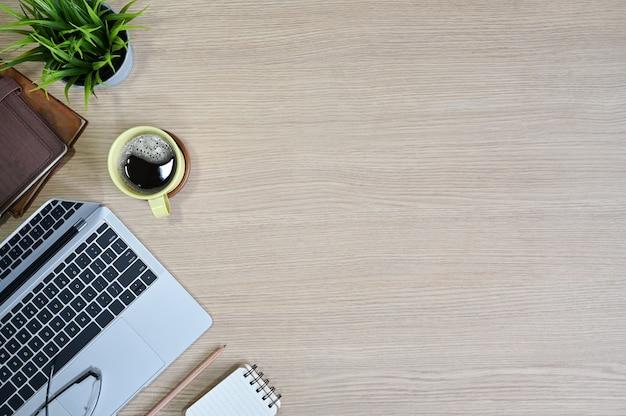 Opinião superior do espaço de trabalho com laptop, café, vidros, livros e decoração da planta na tabela da madeira do escritório.