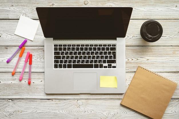 Opinião superior do espaço de trabalho da tabela do escritório. mesa de madeira com laptop, dispositivos e plantas