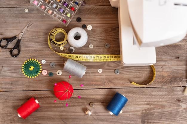Opinião superior do fundo da costureira ou do alfaiate com ferramentas sewing, linhas coloridas, máquina de costura.