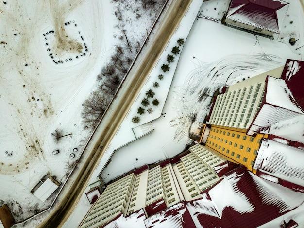 Opinião superior do inverno aéreo do prédio de apartamentos grande moderno na área de subúrbio na estrada suja estreita e no campo nevado.