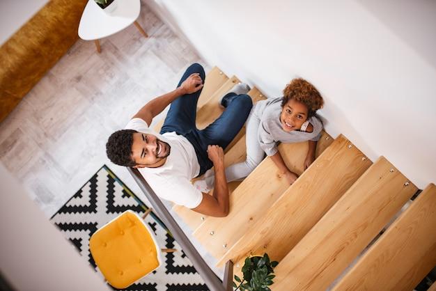 Opinião superior o pai e a filha que sentam-se nas escadas em casa, olhando a câmera.