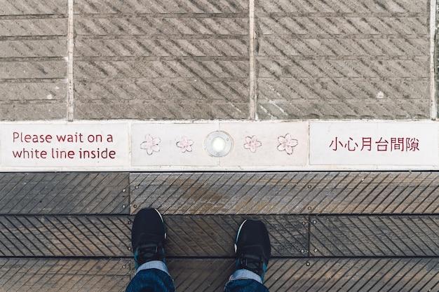 Opinião superior um homem que está na plataforma da estação de trem de zhaoping com palavras de advertência no idioma inglês e chinês e flores decoradas em alishan, taiwan.