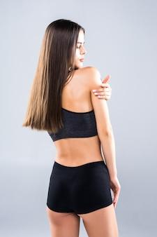 Opinião traseira a jovem mulher atrativa no sportswear que levanta no cinza. modelo feminino magro e saudável em estúdio.
