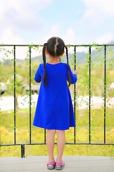 Opinião traseira a menina que está em barras do balcão e que olha para fora à natureza na manhã.