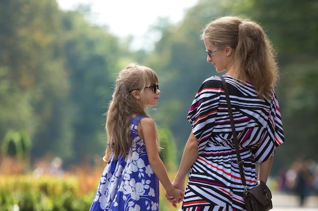 Opinião traseira a mulher atrativa de cabelos compridos loura nova e a menina da criança pequena que guardam as mãos fora.