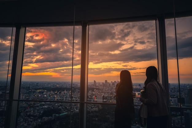 Opinião traseira a mulher do viajante que olha a skyline do tóquio e a vista dos arranha-céus na plataforma de observação no por do sol em japão.
