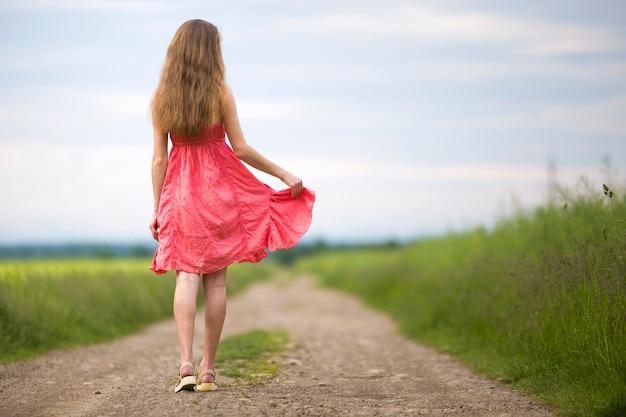 Opinião traseira a mulher magro romântica nova no vestido vermelho com cabelo longo que anda pela estrada à terra ao longo do campo verde no dia de verão ensolarado no espaço da cópia do céu azul.