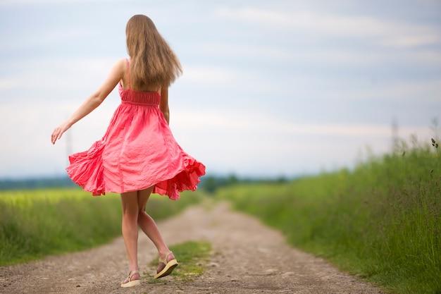 Opinião traseira a mulher magro romântica nova no vestido vermelho com cabelo longo que anda pela estrada à terra ao longo do campo verde no dia de verão ensolarado no fundo do espaço da cópia do céu azul.