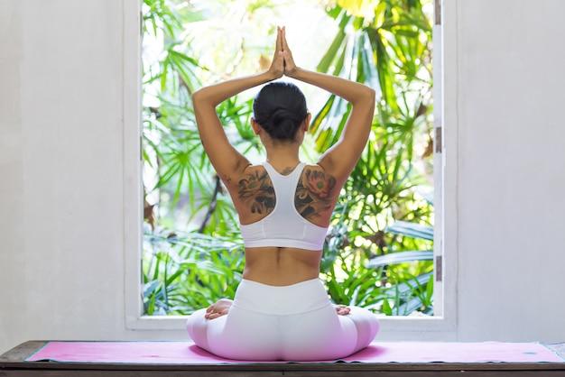 Opinião traseira a mulher que faz o pose da ioga na janela.