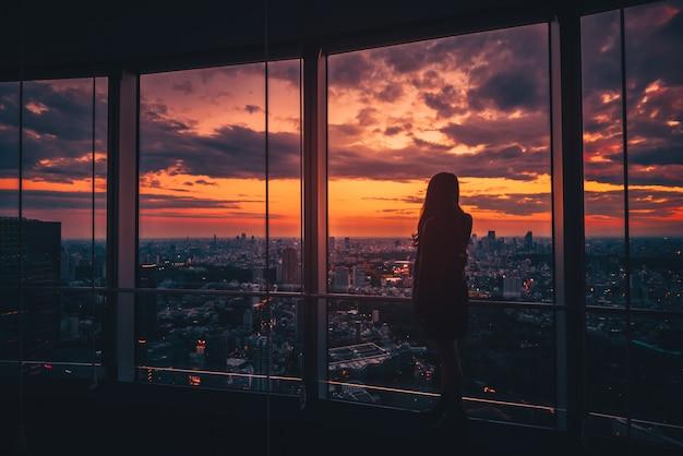 Opinião traseira a mulher que olha a skyline do tóquio e a vista dos arranha-céus na plataforma de observação no por do sol no japão. tom vintage