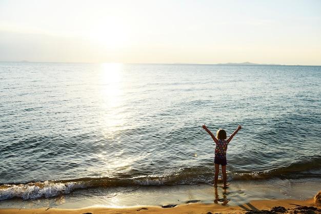 Opinião traseira da silhueta da menina caucasiano nova com os braços levantados na praia apenas