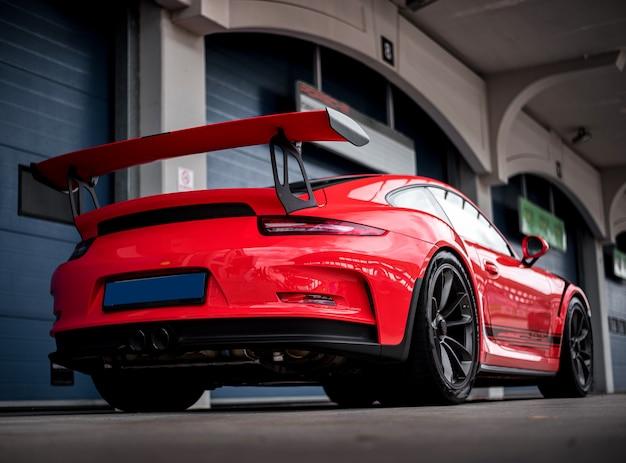 Opinião traseira do carro desportivo vermelho do sedan, estando na estrada.