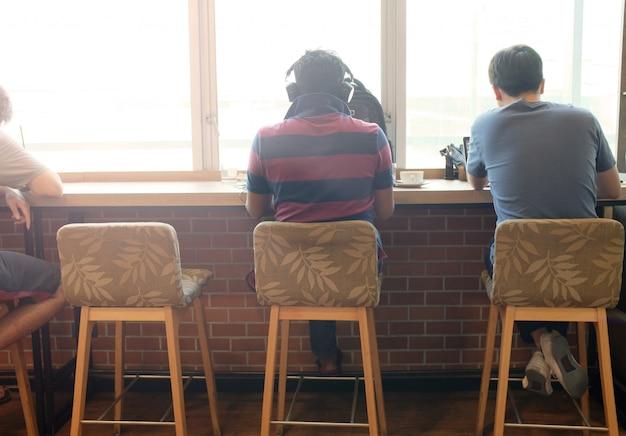 Opinião traseira o adulto que senta-se na cadeira e que usa meios espertos no café.