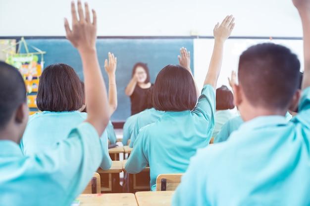 Opinião traseira o estudante asiático que senta-se na classe e que levanta a mão para fazer a pergunta durante a leitura.